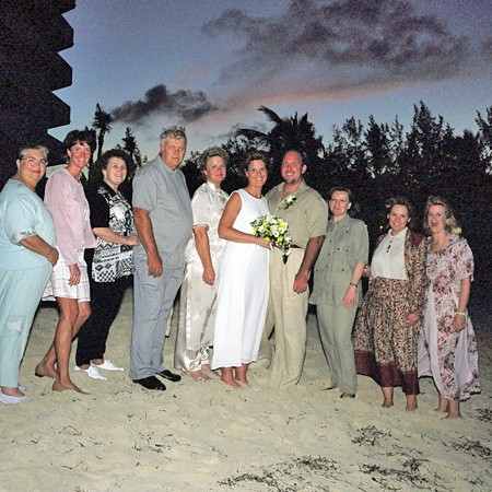 Our wedding party standing on the beach at sunset.
